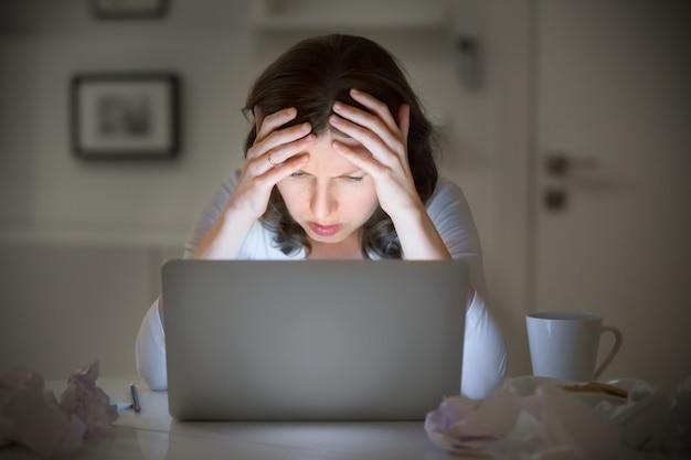 Porträt einer frau packte ihren kopf in der nähe des laptops Kostenlose Fotos