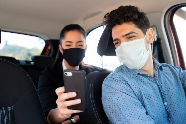 Porträt einer geschäftsfrau, die dem taxifahrer etwas auf seinem telefon zeigt. Premium Fotos