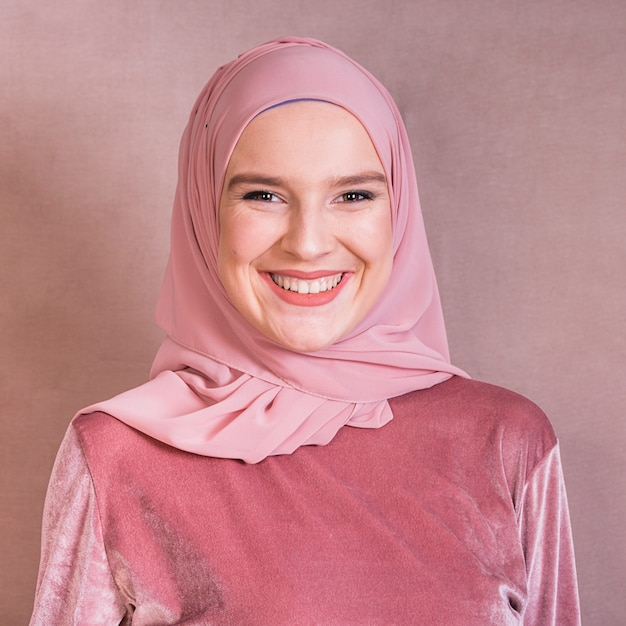 Porträt einer glücklichen arabischen frau gegen farbigen hintergrund Premium Fotos