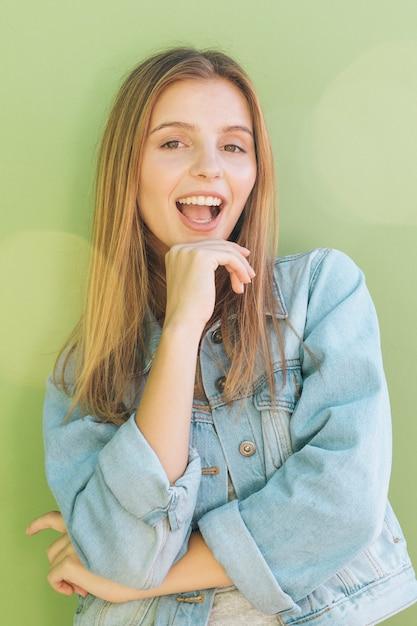 Porträt einer glücklichen blonden jungen frau gegen tadellosen grünen hintergrund Kostenlose Fotos