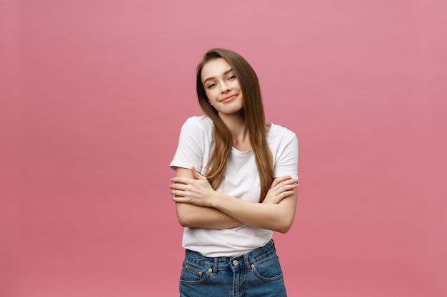 Porträt einer glücklichen frau, die mit den armen steht, faltete sich lokalisiert auf einem rosa hintergrund Premium Fotos