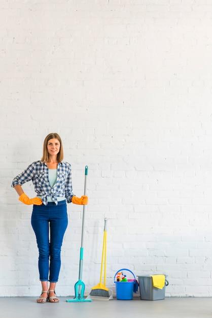 Porträt einer glücklichen frau, die mopp vor backsteinmauer hält Kostenlose Fotos