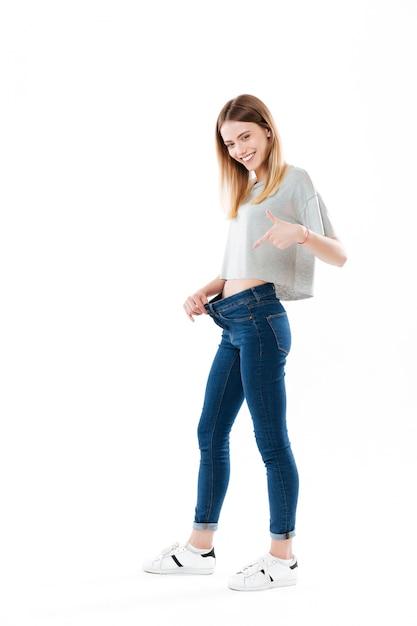 Porträt einer glücklichen freudigen jungen frau, die ihren gewichtsverlust zeigt Kostenlose Fotos