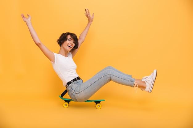 Porträt einer glücklichen fröhlichen frau, die auf einem skateboard sitzt Kostenlose Fotos