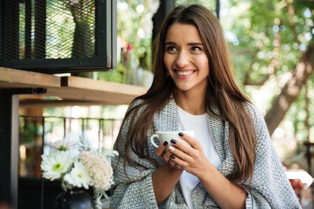 Porträt einer glücklichen fröhlichen frau, die in warme decke gewickelt wird Kostenlose Fotos
