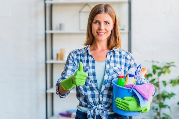 Porträt einer glücklichen hausgehilfin mit eimer von den reinigungsausrüstungen daumen oben gestikulierend Kostenlose Fotos