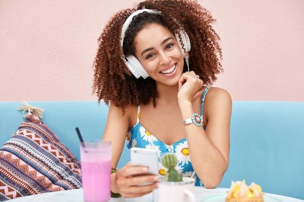Porträt einer glücklichen jungen afroamerikanerin mit knackigem dunklem haar, hört radiosendung, verbunden mit modernem smartphone und weißen kopfhörern Kostenlose Fotos
