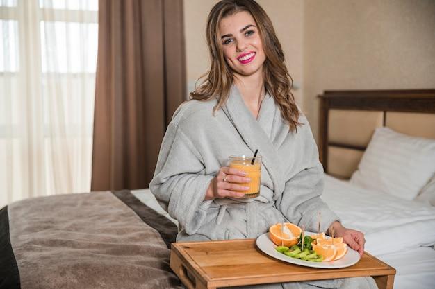 Porträt einer glücklichen jungen frau, die auf dem bett hält glas saft und gesunde scheiben von früchten auf platte sitzt Kostenlose Fotos