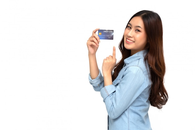 Porträt einer glücklichen jungen frau, die geldautomaten oder debit- oder kreditkarte hält und für online-einkäufe verwendet, die viel geld isoliert über weißer wand, asiatisches weibliches modell ausgeben Premium Fotos