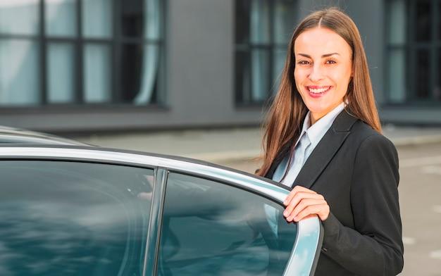 Porträt einer glücklichen jungen geschäftsfrau, die nahe offener autotür steht Kostenlose Fotos