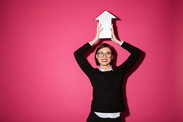 Porträt einer glücklichen jungen geschäftsfrau, die papierpfeilzeichen hält Kostenlose Fotos