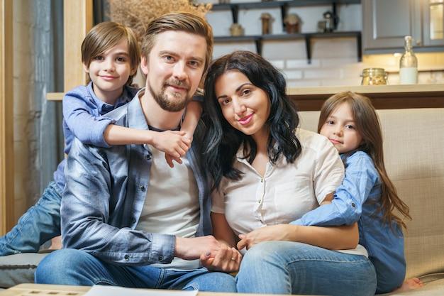 Porträt einer glücklichen lächelnden familie zu hause. nette kleine kinder jungen und mädchen, die ihre eltern umarmen Premium Fotos