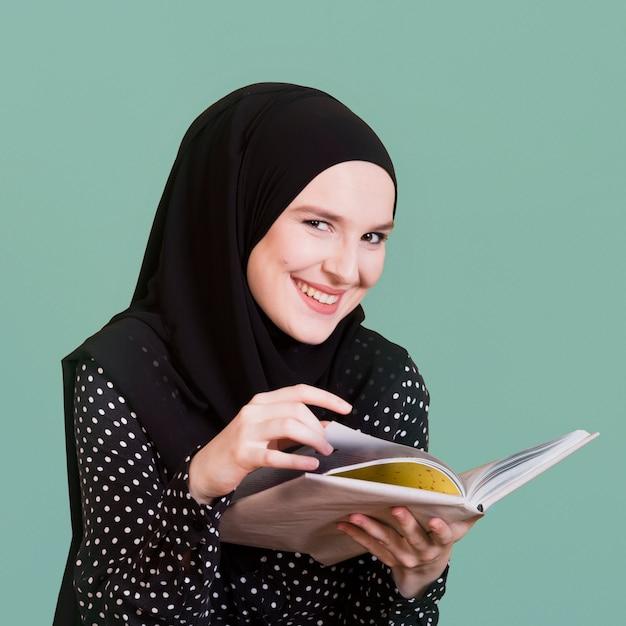 Porträt einer glücklichen moslemischen frau, die in der hand buch hält Kostenlose Fotos