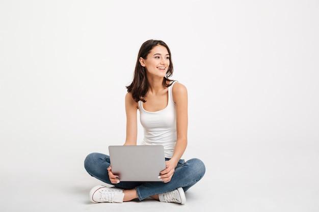 Porträt einer heitren frau kleidete im trägershirt an, das laptop hält Kostenlose Fotos
