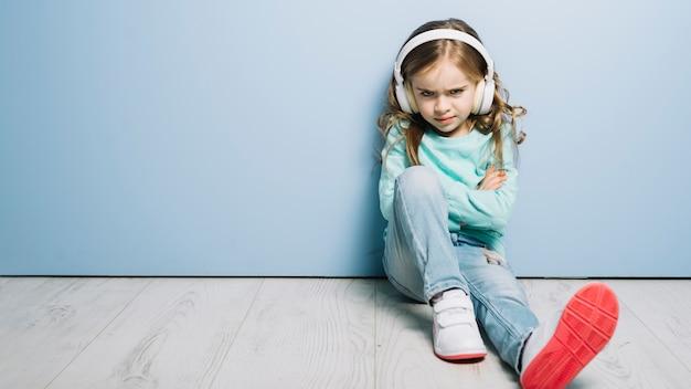 Porträt einer hörenden musik des verärgerten mädchens auf dem kopfhörer, der kamera betrachtet Kostenlose Fotos