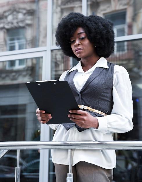 Porträt einer jungen afrikanischen geschäftsfrau, die vor dem geländer hält klemmbrett steht Kostenlose Fotos
