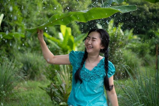 Porträt einer jungen asiatischen frau mit schwarzen haaren, die ein bananenblatt im regen halten Premium Fotos