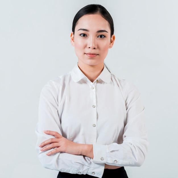 Porträt einer jungen asiatischen geschäftsfrau mit ihrem arm kreuzte das schauen zur kamera, die auf weißem hintergrund lokalisiert wurde Kostenlose Fotos
