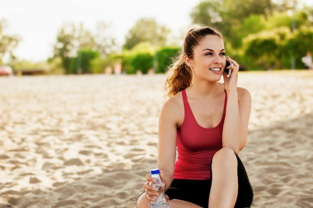 Porträt einer jungen attraktiven frau, die am handy beim sitzen auf dem strand spricht Premium Fotos