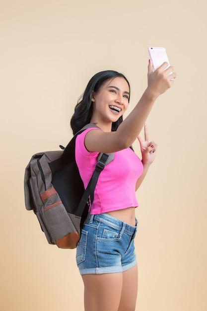 Porträt einer jungen attraktiven frau, die selfie foto mit smartphone macht Kostenlose Fotos