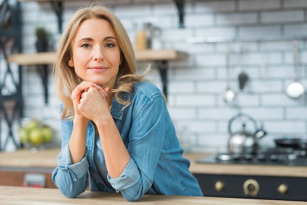 Porträt einer jungen blonden frau, die kamera betrachtet Kostenlose Fotos