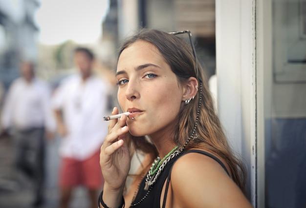 Porträt einer jungen frau, die auf der straße raucht Kostenlose Fotos