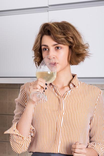 Porträt einer jungen frau, die den wein trinkt Kostenlose Fotos