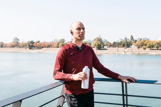 Porträt einer jungen frau, die in der hand nahe dem see hält wasserflasche steht Kostenlose Fotos