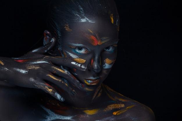 Porträt einer jungen frau, die mit schwarzer farbe bedeckt posiert Kostenlose Fotos