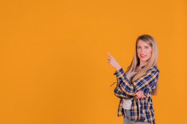 Porträt einer jungen frau, die seinen finger gegen einen orange hintergrund zeigt Kostenlose Fotos