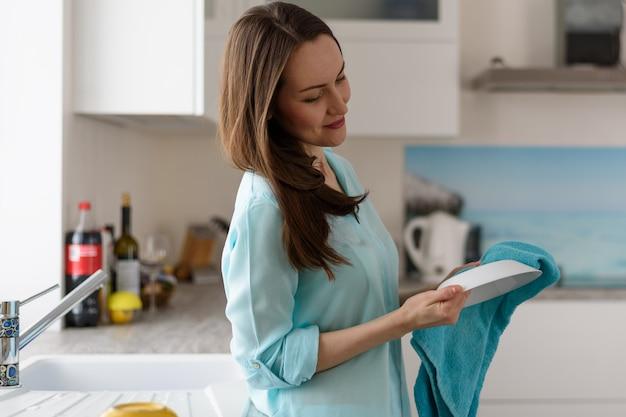 Porträt einer jungen frau im kücheninnenabwischen mit sauberen tellern eines trockenen tuches, das haus säubernd Premium Fotos