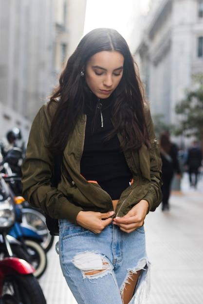 Porträt einer jungen frau, welche die jacke auf der straße reißverschluss macht Kostenlose Fotos