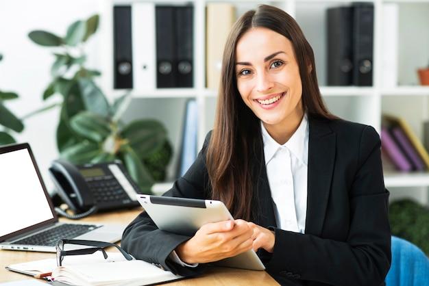Porträt einer jungen geschäftsfrau, die am schreibtisch hält digitale tablette in ihrer hand sitzt Kostenlose Fotos