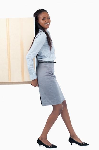 Porträt einer jungen geschäftsfrau, die zurück eine platte mit ihr drückt Premium Fotos