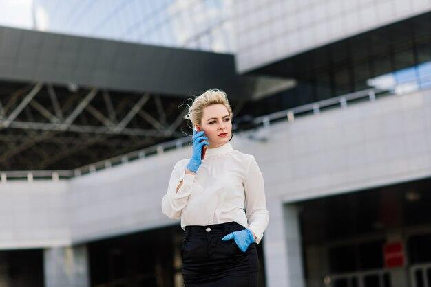Porträt einer jungen geschäftsfrau mit telefon, notizbuch, tablette, kaffee im freien. blondes mädchen in blauen gummihandschuhen. Premium Fotos