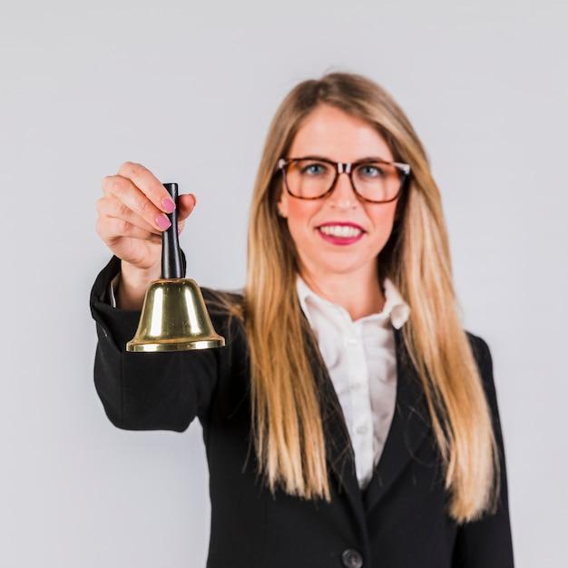 Porträt einer jungen geschäftsfrau, welche die goldene glocke auf grauem hintergrund hält Kostenlose Fotos