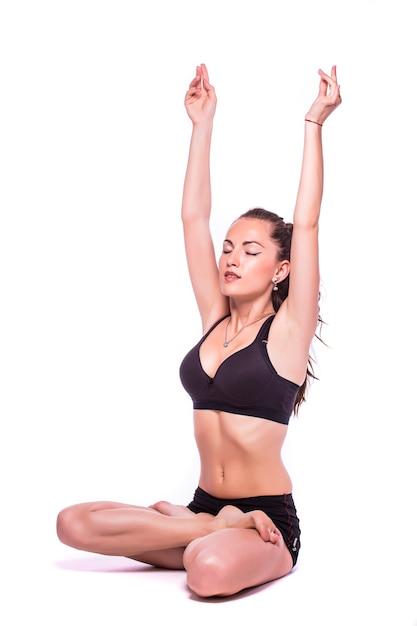 Porträt einer jungen gesunden frau, die yoga-übungen macht, lokalisiert über weißem hintergrund Kostenlose Fotos