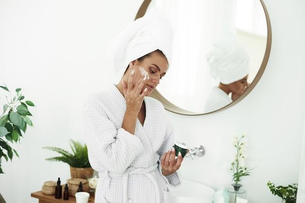 Porträt einer jungen lächelnden frau, die feuchtigkeitscreme auf ihr gesicht im badezimmer anwendet. kosmetologie. schönheit und spa. Premium Fotos