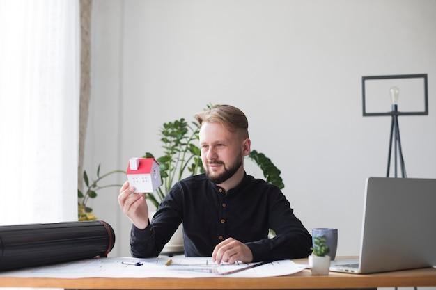 Porträt einer jungen männlichen architektur, die hausmodell beim sitzen im büro hält Kostenlose Fotos