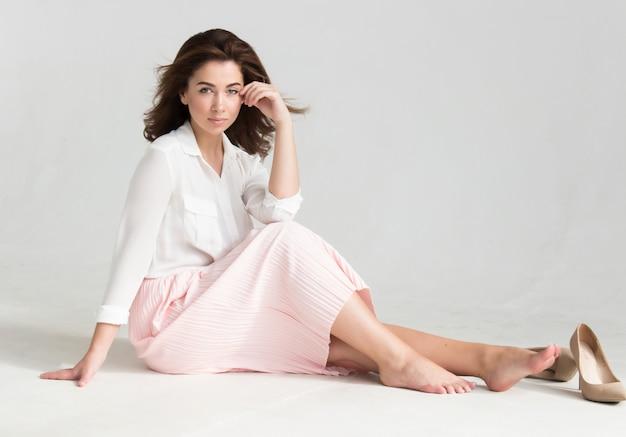 Porträt einer jungen schönen braunen behaarten frau in einer weißen bluse und in einem rosa rock, die auf dem boden sitzen Premium Fotos