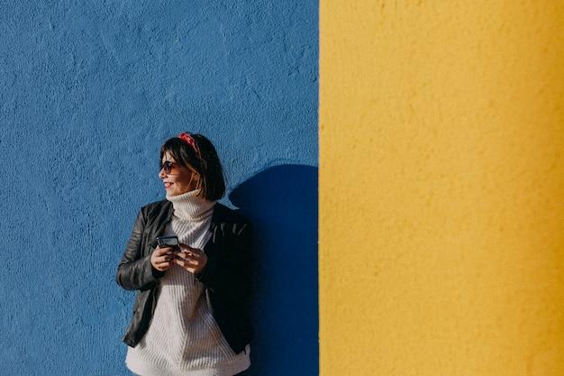 Porträt einer jungen schönheit, die draußen handy über blauem und gelbem hintergrund verwendet Premium Fotos