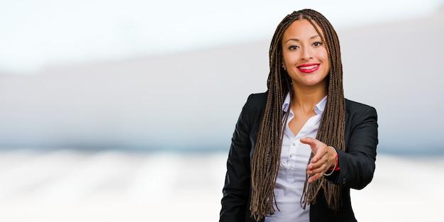 Porträt einer jungen schwarzen geschäftsfrau, die heraus erreicht, um jemand zu grüßen oder zu gestikulieren, um zu helfen, glücklich und aufgeregt Premium Fotos