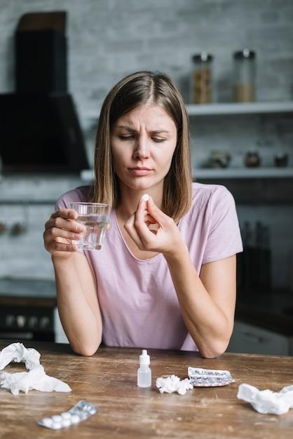 Porträt einer kranken jungen frau mit glas wasser und medizin Kostenlose Fotos