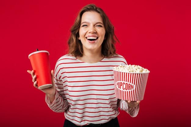 Porträt einer lachenden frau, die popcorn hält Kostenlose Fotos