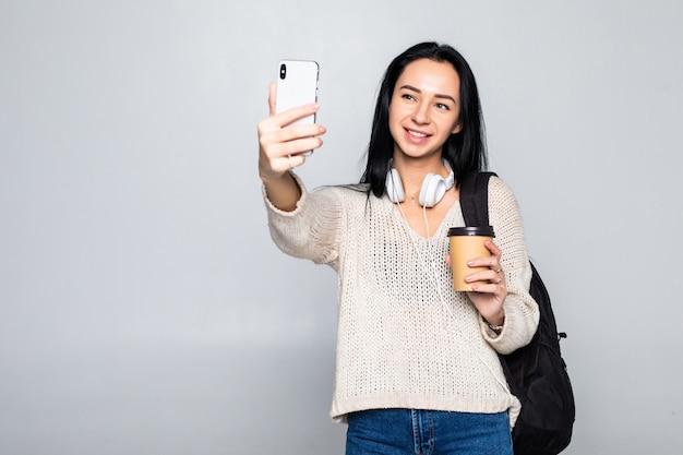 Porträt einer lächelnden attraktiven frau, die ein selfie nimmt, während kaffeetasse wegnehmen isoliert über weißer wand hält Kostenlose Fotos