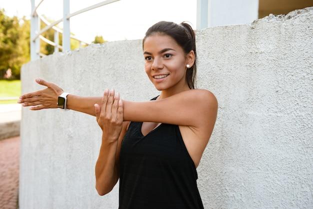 Porträt einer lächelnden fitnessfrau, die ihre hände streckt Kostenlose Fotos