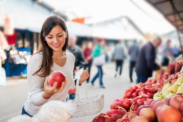 Porträt einer lächelnden frau, die lebensmittelmarkt am im freien kauft. Premium Fotos