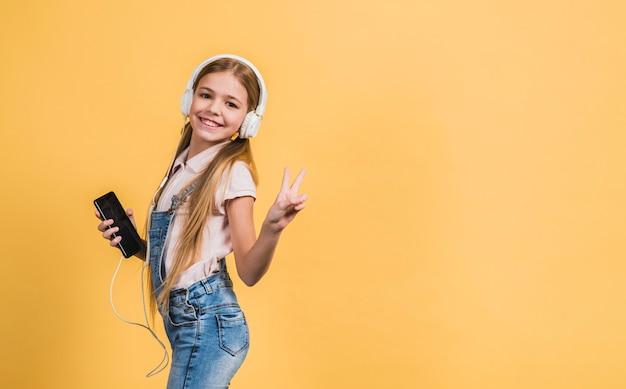 Porträt einer lächelnden hörenden musik des mädchens auf dem weißen kopfhörer, der gegen gelben hintergrund gestikuliert Kostenlose Fotos