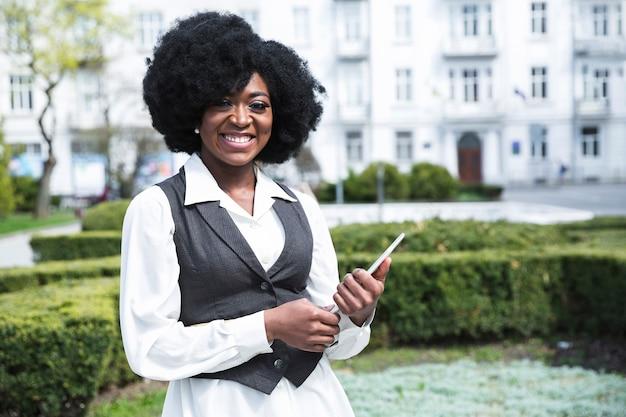 Porträt einer lächelnden jungen afrikanischen geschäftsfrau, die digitale tablette hält Kostenlose Fotos