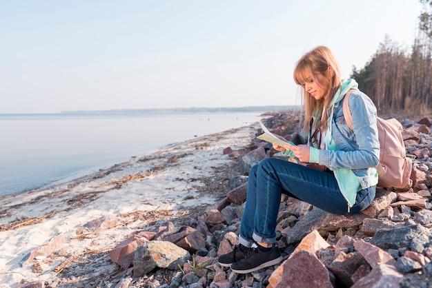 Porträt einer lächelnden jungen frau, die auf dem strand betrachtet karte sitzt Kostenlose Fotos